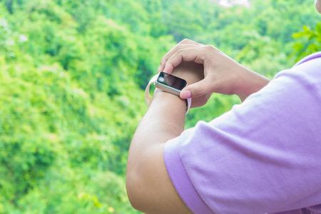 Hand of Fat Asian Woman use Bracelet Smart Watch over the Mountain in Tropical Forest Nature with Cloudy Blue Sky as Freedom Outdoor Digital Modern Lifestyle Concept. Stok Fotoğraf