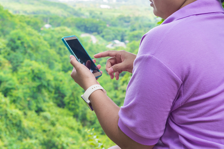 Hand of Fat Asian Women use Cell phone or Wireless Mobile Phone over Mountain in Nature with Cloudy blue sky as Freedom Outdoors Travel Lifestyle Concept.