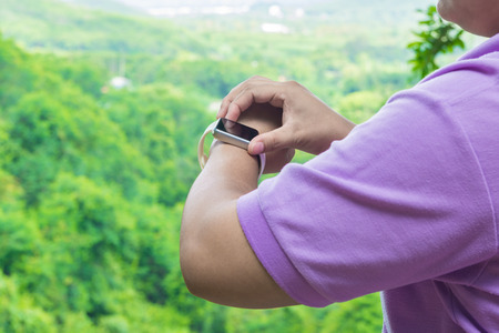 Hand of Fat Asian Woman use Bracelet Smart Watch over the Mountain in Tropical Forest Nature with Cloudy Blue Sky as Freedom Outdoor Digital Modern Lifestyle Concept. Stock Photo
