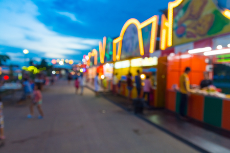 Abstract Blur or Defocus Background image of People Walking in Amusement Fun Park or Fun Fair with Play and Souvenir Shop Surround at Twilight.