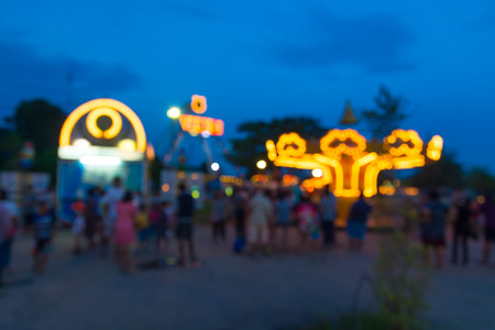 Abstract Blur or Defocus Background image of People, Male Female and Kids, Walking around in Local Amusement Fun Park or Fun Fair in Thailand at Twilight. 免版税图像