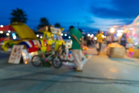 Abstract Blur or Defocus Background image of People, Male and Female, Shopping in Local Night Market in Thailand at Twilight.