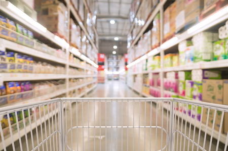 Trolley Shopping Cart Between Dry Grocery Shelf Section in Supermarket or Hypermarket Warehouse Retail Outlet as Modern Lifestyle Shopping Concept with bokeh. Stok Fotoğraf