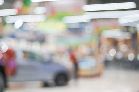 Blur or defocused background of public event exhibition hall showing cars and automobiles, business commercial event concept