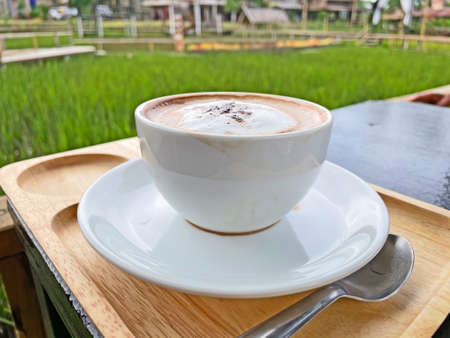 Hot coffee latte macchiato , Hot coffee cup with farm view.