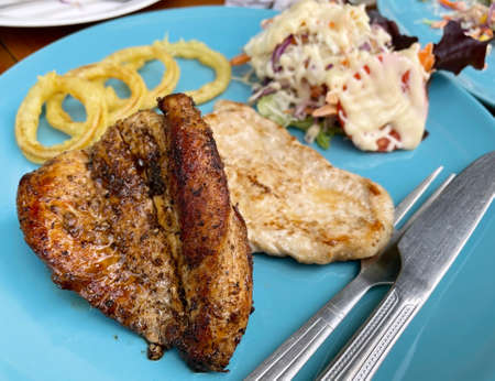 Grilled pork steak with salad and onion rings
