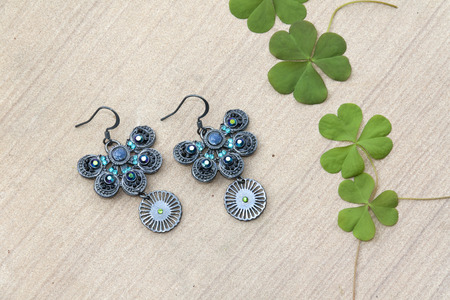 Beautiful butterfly shape earring and green leaves photo