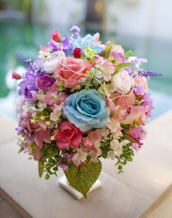Beautiful pink and blue flower bouquet with swimming pool background photo