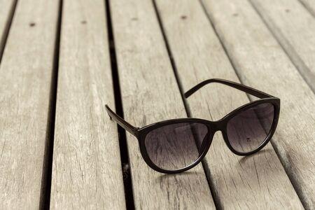 Vintage tone A sunglasses on wooden floor photo