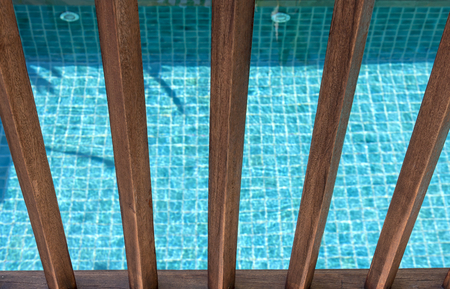 Wooden fence with blue swimming pool background