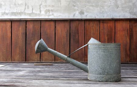 watering pot: Metal watering pot with red wood wall background