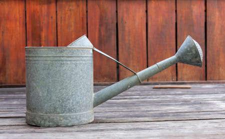 watering pot: Metal watering pot side on red wood wall Stock Photo
