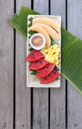vertica: Colorful Thai fresh fruit in season on banana leaf vertica