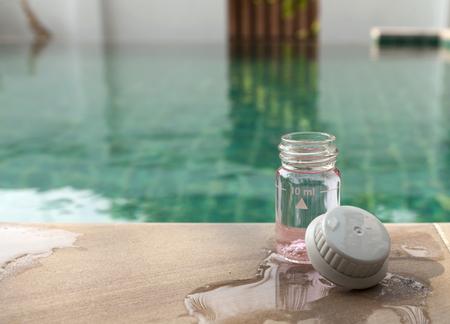 balanza de laboratorio: Botella de vidrio de la prueba de agua con espacio en la piscina Foto de archivo