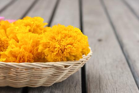 wood floor: Closeup Yellow marigold in rattan basket with space on the wood floor