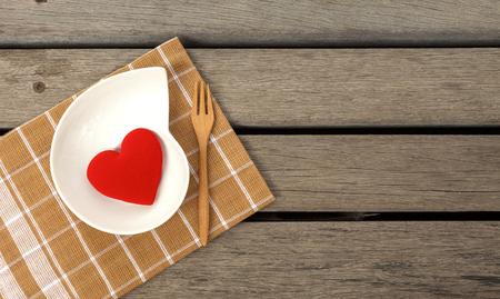 wood floor: Red heart on brown napkin with space on wood floor