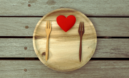 Red heart on wooden plate Standard-Bild
