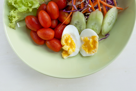 protien: Fresh vegetable salad with egg in green plate on wood background