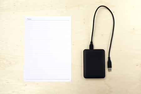 external: White note and external hard drive on wood background Stock Photo