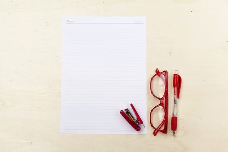 stapling: White note on wood background with eyeglasses and pen Stock Photo