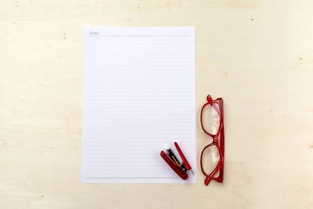 stapling: White note on wood background with red eyeglasses and stapler