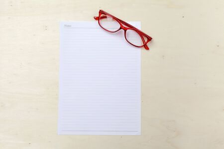 office wear: White note on wood background with red eyeglasses