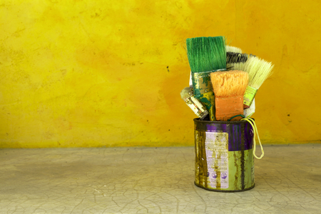 yellow paint: Yellow retro tone the old paint brush in rusty tin with space on cement wall