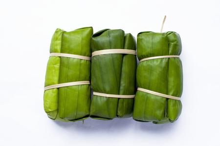 string together: Thai style dessert in fresh banana leaf on white background