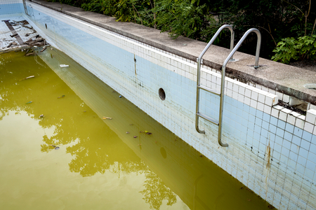 Dirty water in old concrete swimming pool