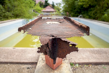gunk: Rusty steel with old swimming pool background Stock Photo