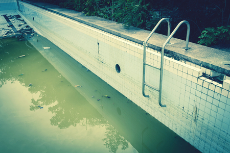 Dirty water in old concrete swimming pool vintage tone style