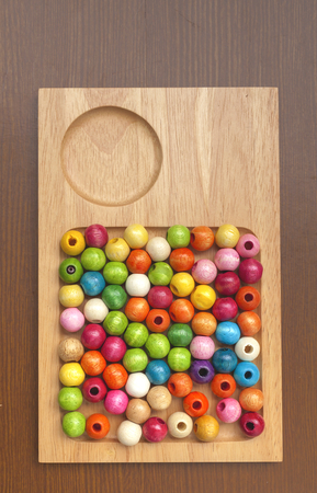 colorful beads: Colorful beads on wooden tray