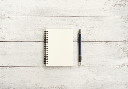 Blank notebook and pen on white wood background