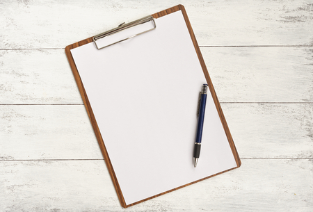 Clipboard and pen on white wood background Standard-Bild