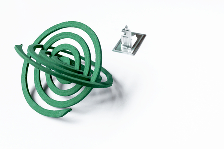 anti season: Green mosquito repellent coils with stand on white background Stock Photo