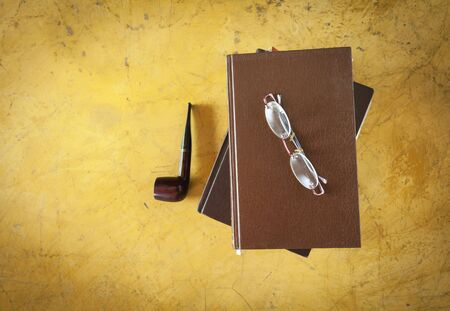 smoking pipe: Eyeglasses on old book and smoking pipe on vintage style background