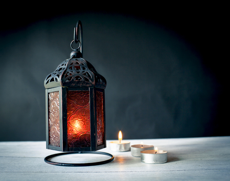 Design metal lantern with candle light and dark background