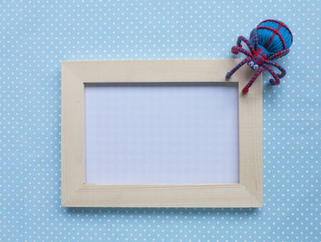 wood spider: Wood frame with red and blue spider on blue background