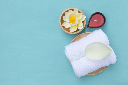 Home spa concept background, white towels with red candle and flower with space on blue background Stok Fotoğraf - 52953956