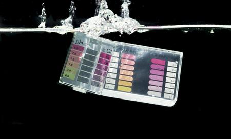 balanza de laboratorio: Nataci�n prueba kit de agua de la piscina de inmersi�n en agua con el fondo negro Foto de archivo
