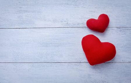 Two red hearts with space on white wood background