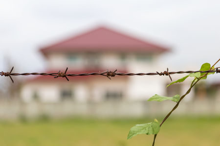 Rusty Barbed wire fence with blur big house on background Stock Photo