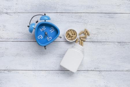 Blue clock with herb capsule on white wood background 版權商用圖片