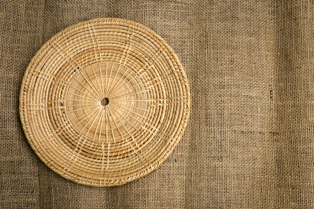 hessian: Round rattan tray on hessian texture background