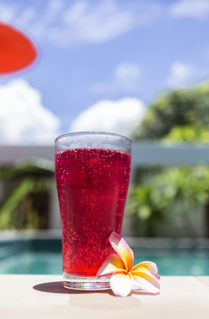 Red soda water at poolside in summer sunny day