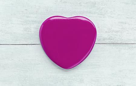 metal box: Pink heart shape metal box lid on white wood background