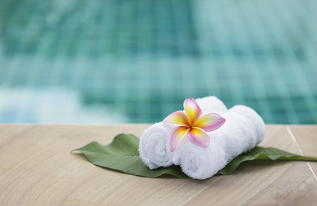hand towel: Spa concept background, plumeria flower on white hand towel with swimming pool background