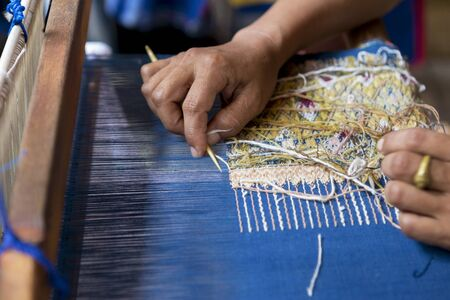 handloom: Thai girl using quill for weaving famose traditional northern thai sarong Stock Photo