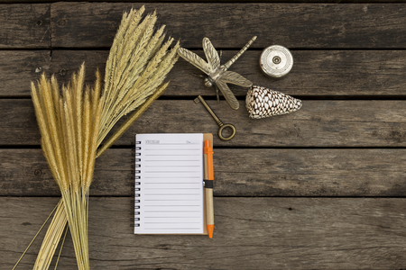 yellow notepad: Vintage concept background, blank notebook with grass flower and old key on wooden floor background