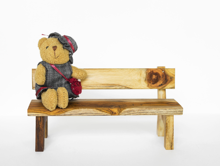Little teddy bear sitting on wooden bench on white background